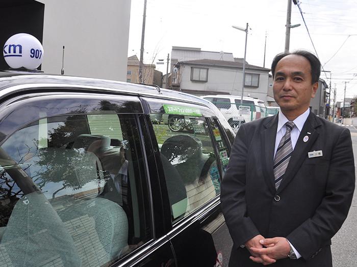 タクシーの横に立つ国際自動車(㎞タクシー)の稼げるタクシードライバー三橋さんの写真