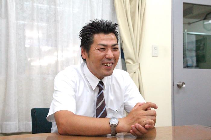 笑顔で話をしているケイエム観光バス株式会社のバスドライバー阿部さんの写真
