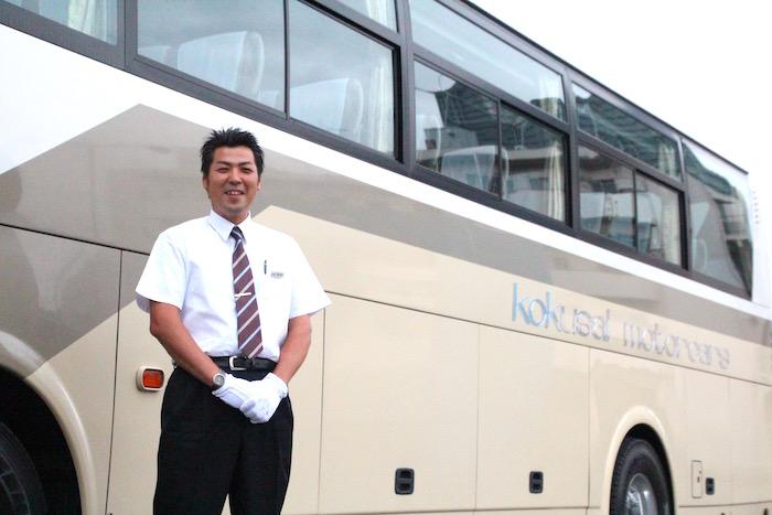 観光バスを背に笑顔で立っている、ケイエム観光バス株式会社のバスドライバー阿部さんの写真