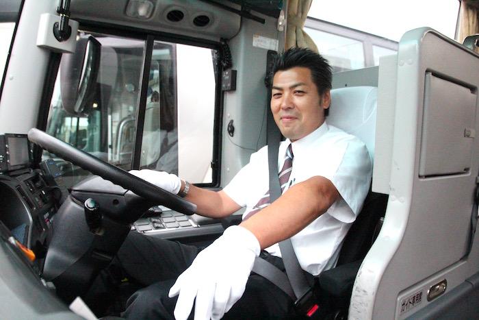 運転席で笑顔を向けるケイエム観光バス株式会社のバスドライバー阿部さんの写真