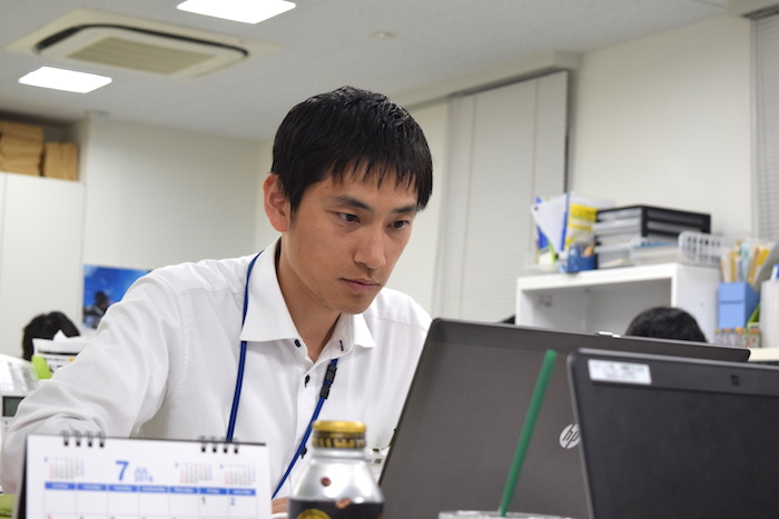 国際自動車(㎞タクシー)の元タクシードライバーで現在は人財採用課(人事)の福島さんが、パソコンを真剣に見つめている写真