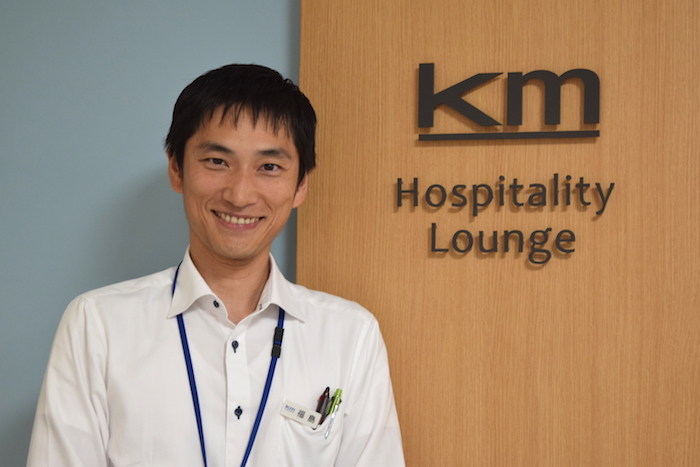 「km Hospitality Lounge」の文字が掲げられた壁の前に笑顔で立っている、国際自動車(㎞タクシー)の元タクシードライバーで現在は人財採用課(人事)の福島さんの写真