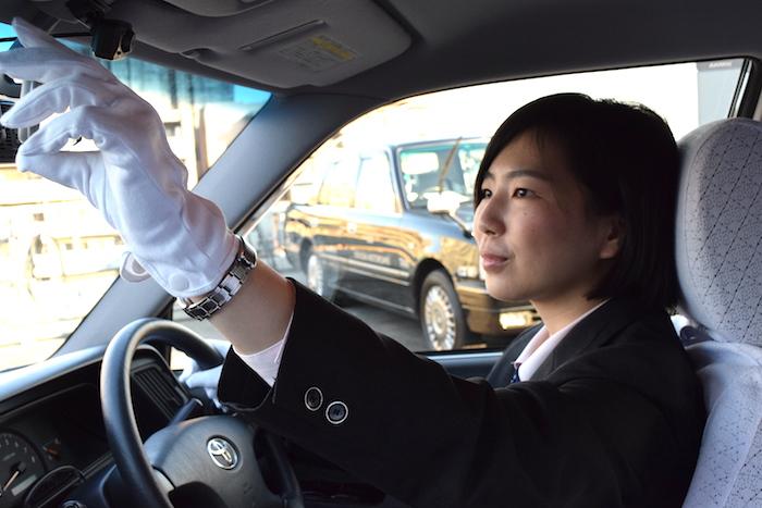 タクシーの運転席でミラーの向きを確認している成毛さんの写真