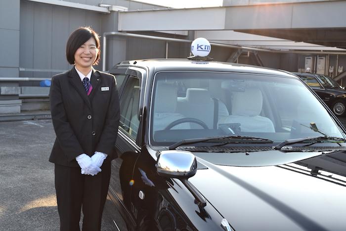 タクシーの横に笑顔で立っている、国際自動車(kmタクシー)の女性タクシードライバーで、新卒女性班長の成毛さんの写真