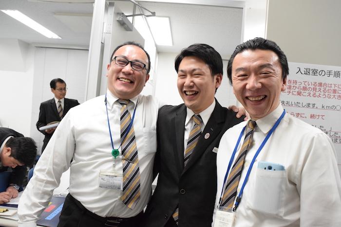 国際自動車(kmタクシー)の人財研修課の同僚二人と、肩を組んで満面の笑みを浮かべている小野さんの写真