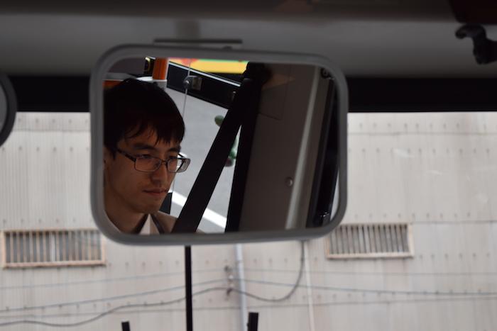 ミラー越しの25歳新人路線バスドライバーの大滝さん