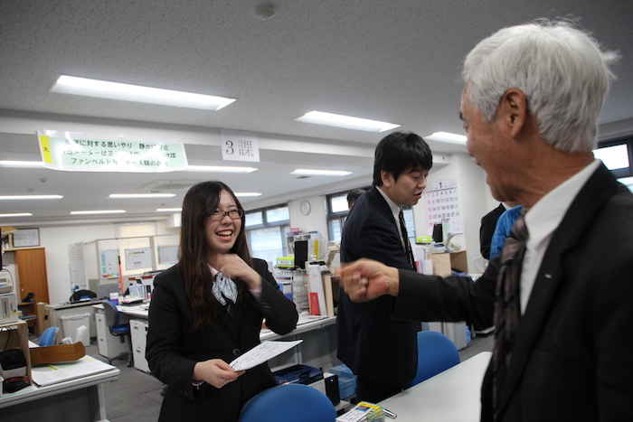 同僚と笑顔で話をする田島さんの写真