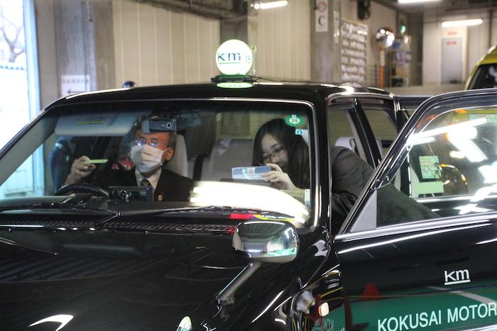 タクシーの助手席で作業している国際自動車(kmタクシー)株式会社板橋営業所職員の田島さんの写真