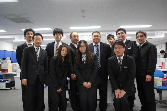 国際自動車(kmタクシー)株式会社板橋営業所の同僚と一緒に笑顔で写真にうつる田島さん