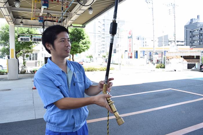LPガススタンドで使用するノズルを持つ、国際自動車(㎞タクシー)のLPガススタンドで働く武原さんの写真