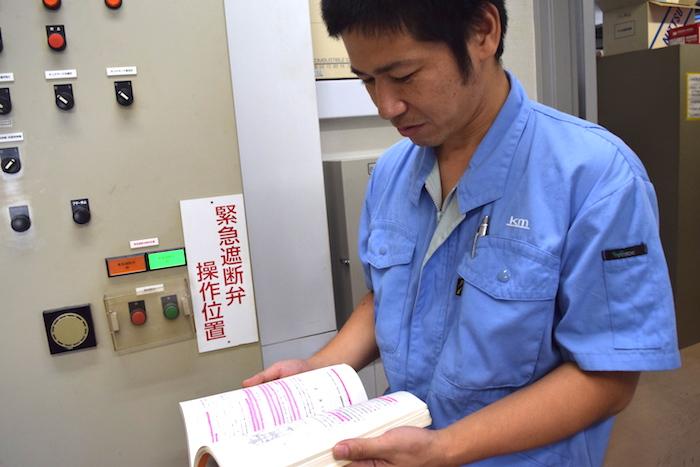 本を真剣に見ている武原さんの写真