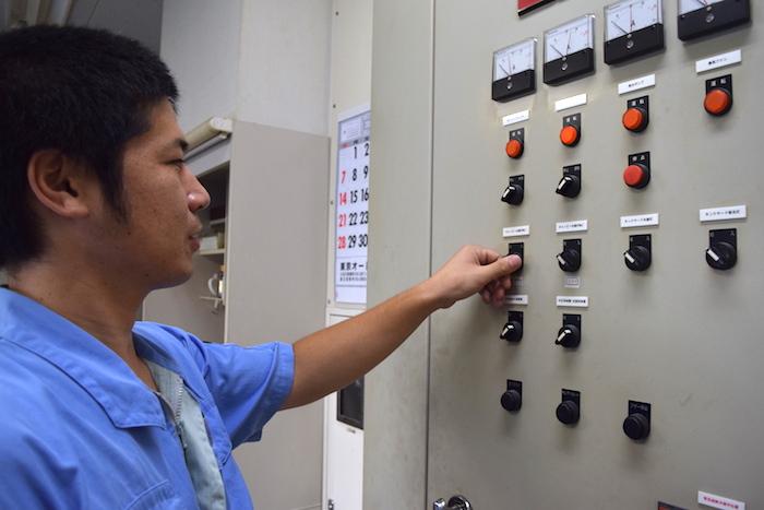 スイッチがたくさん並んだ機械の前にたって作業している武原さんの写真