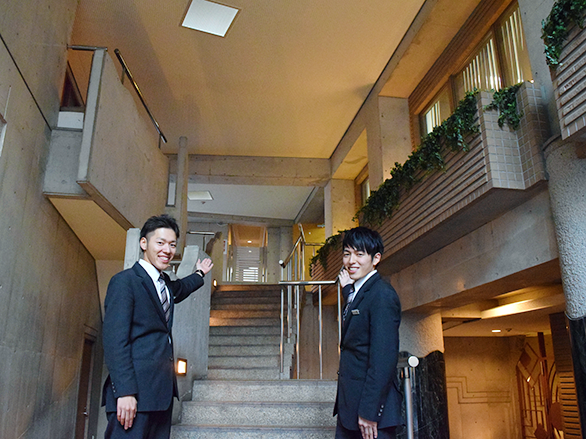 エントランスを紹介するポーズをとっている、国際自動車(㎞タクシー)のタクシードライバー石垣さんと小野さんの写真