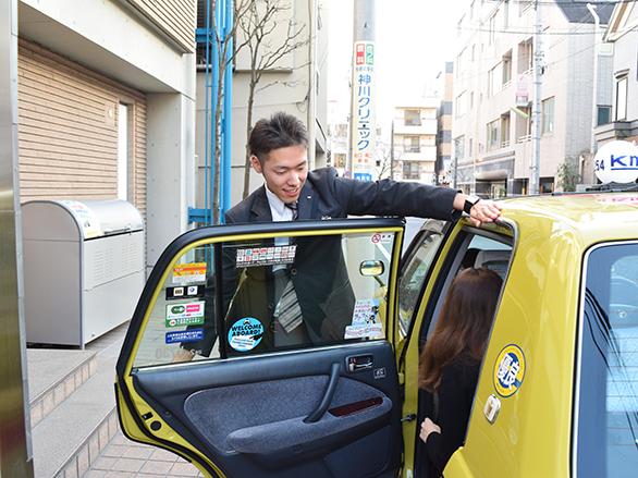 国際自動車(㎞タクシー)のタクシードライバー石垣さんがドアサービスをしている写真
