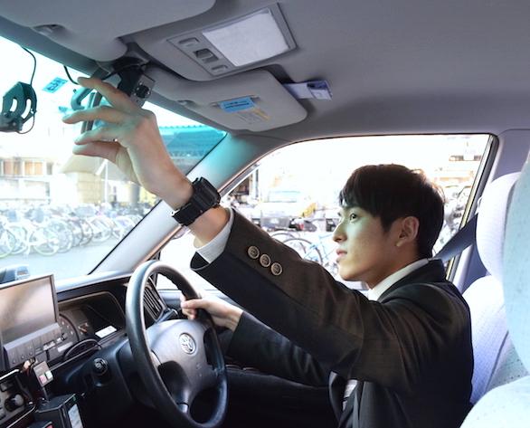 国際自動車(kmタクシー)の中途タクシードライバー小野さんのフロントミラーを調整している写真