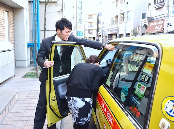 国際自動車(kmタクシー)の中途タクシードライバー小野小野裕貴さんのドアーサービスをしている写真