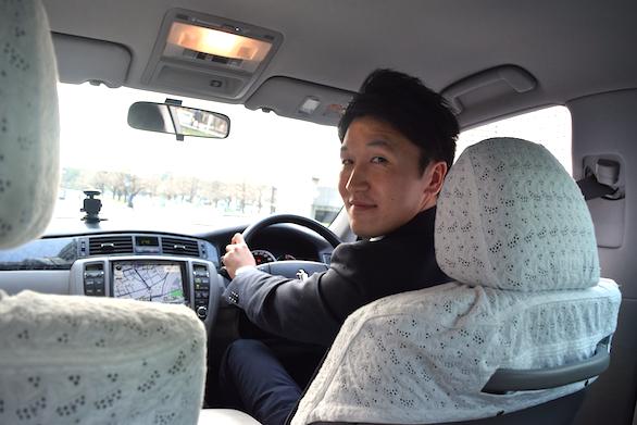 国際ハイヤー株式会社のイケメンハイヤードライバーの斉藤さんが後部座席に振り向いている写真