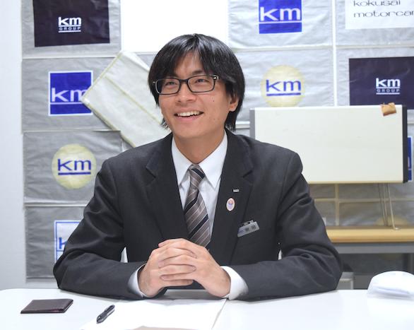笑顔で話をしている、国際自動車(㎞タクシー)に仮面就職で入社したバンドマンのタクシードライバー安田さんの写真