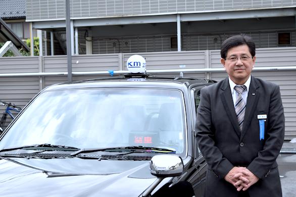 タクシーの横に立つ、国際自動車(㎞タクシー)吉祥寺営業所所属のベテランタクシードライバー橋本さんの写真