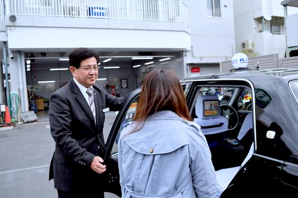 ドアサービスをしている国際自動車(㎞タクシー)吉祥寺営業所所属のベテランタクシードライバー橋本さんの写真