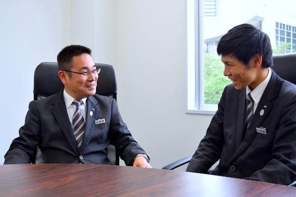 国際ハイヤー株式会社のベテランハイヤードライバー菅野さんと新卒ハイヤードライバー伊藤さんの話をしている写真
