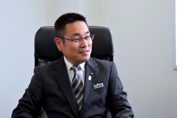国際ハイヤー株式会社のベテランハイヤードライバー菅野さんの笑顔の写真