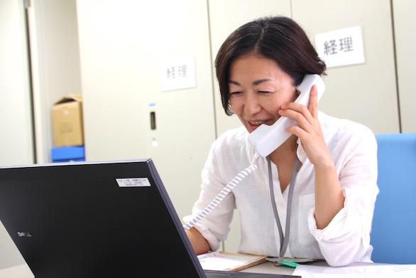 笑顔で電話応対をしている、国際自動車(㎞タクシー)株式会社の健康管理室でドライバーの健康管理に従事する看護師仲野さんの写真
