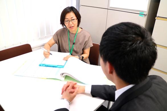 男性のドライバーと面談している、国際自動車(㎞タクシー)の健康管理室でドライバーの健康管理に従事する看護師仲野さんの写真