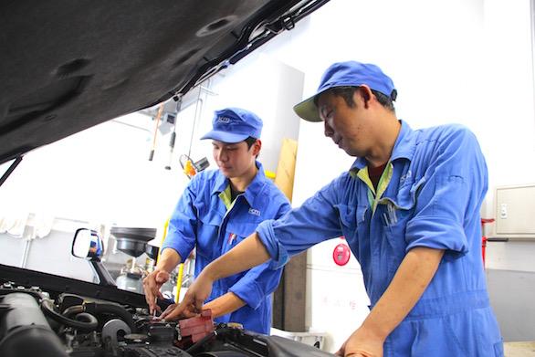 同僚と一緒に整備をしている国際自動車(㎞タクシー)板橋整備工場で働く新卒整備士小林さんの写真