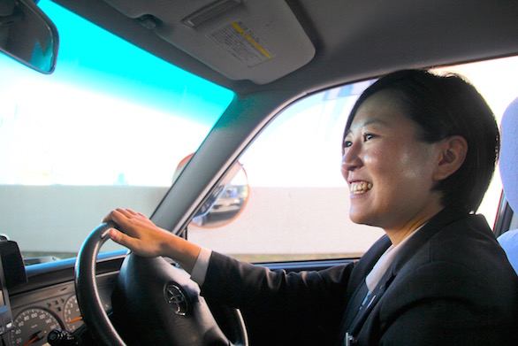 笑顔でタクシーを運転している国際自動車(㎞タクシー)株式会社に第二新卒で入社した女性タクシードライバー河原さんの写真