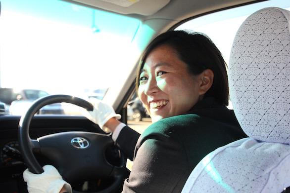 タクシーの運転席から笑顔で振り返る、国際自動車(㎞タクシー)株式会社に第二新卒で入社した女性タクシードライバー河原さんの写真