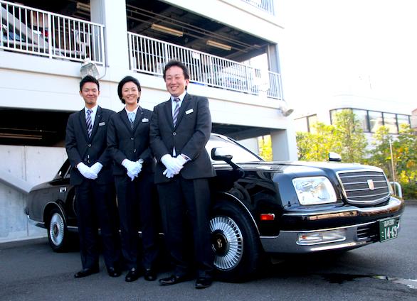 ハイヤーを背に同僚2人と一緒に立っている国際ハイヤー株式会社第二支店所属の女性ハイヤードライバー田邉さんの写真