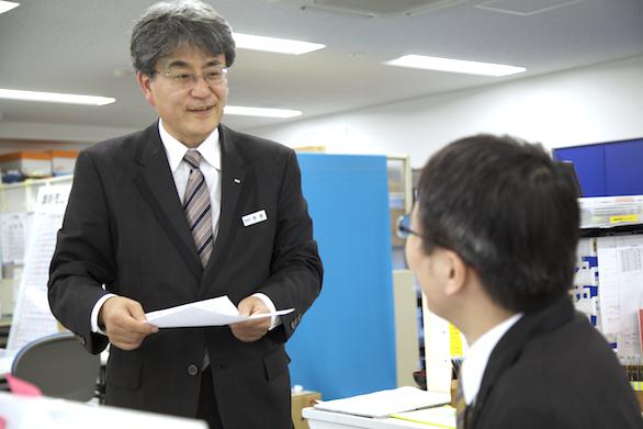 立ちながら、座っている同僚と笑顔で話をしているタクシードライバー本多さんの写真