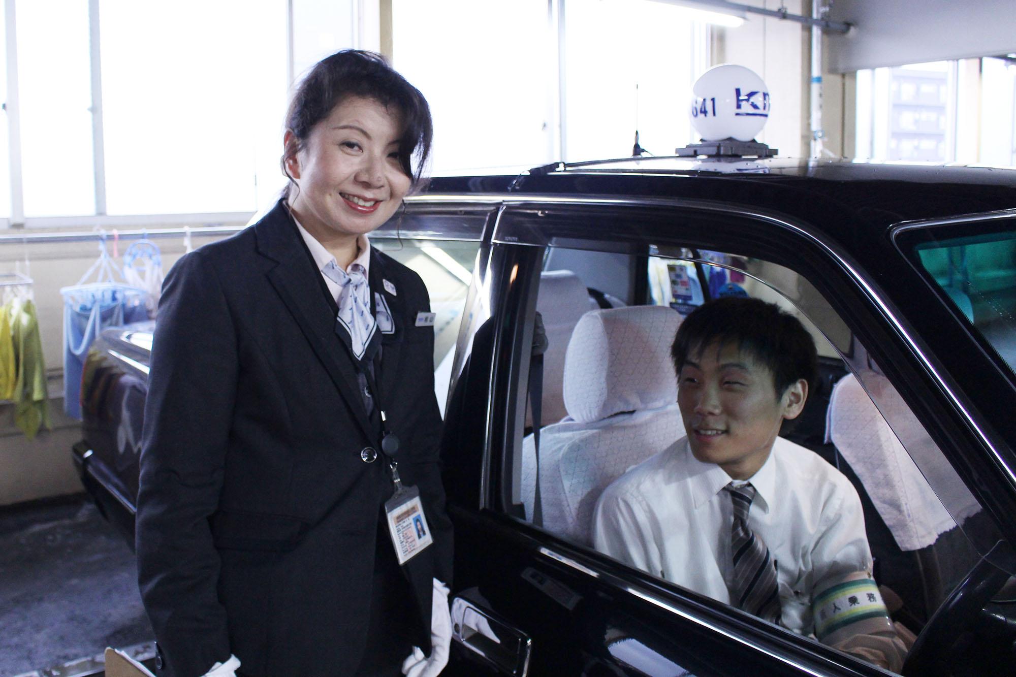 国際自動車(kmタクシー)の女性タクシードライバー相山さんと、羽田営業所の後輩新卒タクシードライバーの写真
